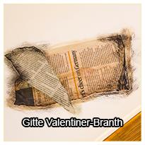 """Gitte Valentiner-Branth demonstrerer, hvordan hun anvender aviser i sin bund, når hun går i gang med nye malerier og hvordan hun skaber en """"brændt"""" effekt på lærredet."""