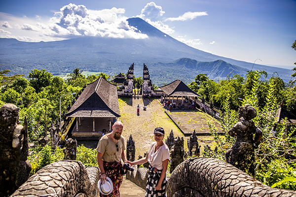 En svedig Jesper og et styk Anne med højdeskræk på tempelbesøg på Bali, med vulkanen Mount Agung i baggrunden :)